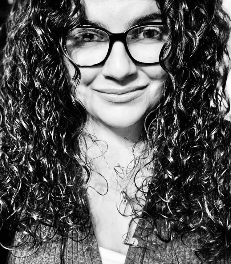 Dominique smiles at the camera. She wears Wayfarer glasses, has long curly brown hair, and wears a silver Southern Italian amulet,. The photo is shot in black and white. She is wearing a blouse and tank top