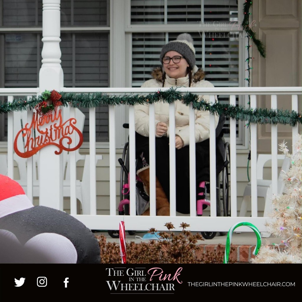 "Dominique, a white Italian woman, is wearing a handmade knit hat, a  beige winter coat, Wayfarer glasses, and Christmas leggings. The porch is decorated with Christmas decorations. Dominique has teary eyes and smiles. She is a wheelchair user; sitting in her wheelchair. Her porch is decorated.   The bottom of the photo has a black edging. The black edging has a text logo of ""The Girl in The Pink Wheelchair"" in the middle. To the left are icons for Twitter, Instagram and Facebook. To the right says thegirlinthepinkwheelchair.com"